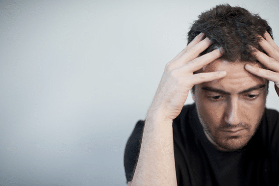 Depressed man looks down while hands on head