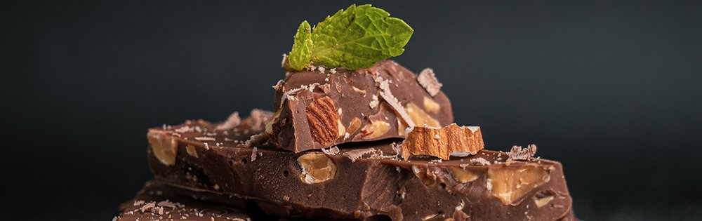stack of chocolate with almonds and mint leaf on top