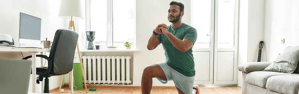 man in green tshirt and grey shorts doing squat at home online workout