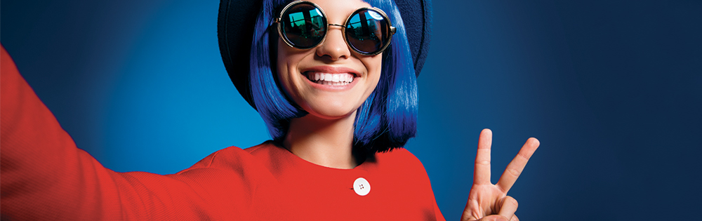 teen girl with blue hair and round sunglasses wears hat and red jacket. She smiles and does the peace sign.