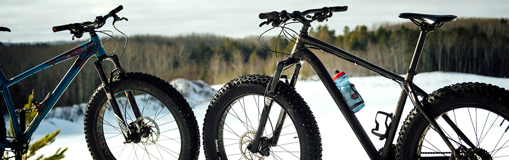 two fat bikes parked on a snowy hill