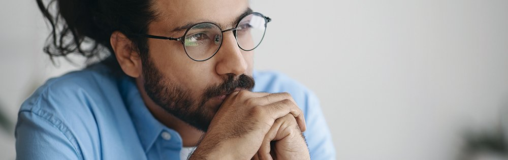depressed or serious man with beard and round glasses sits thinking