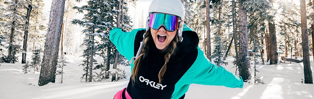 woman ski goggles white helmet teal jacket arms out wide in snowy forrest