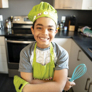 smiling boy wearing green bakers hat, apron and oven mitt, holding whisk