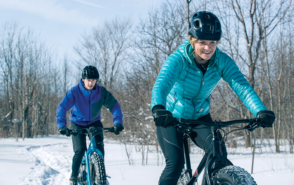 Woman and her teen son ride fat bikes in the snow