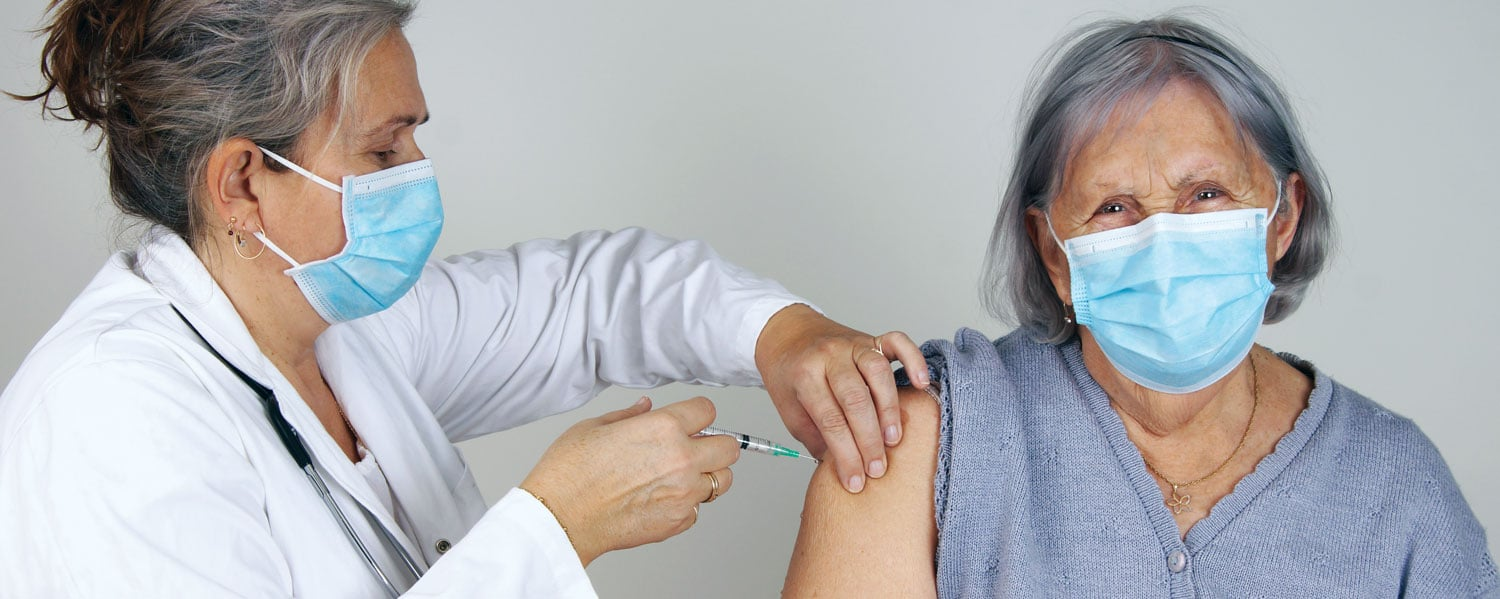 doctor giving vaccine shot to senior woman wearing masks