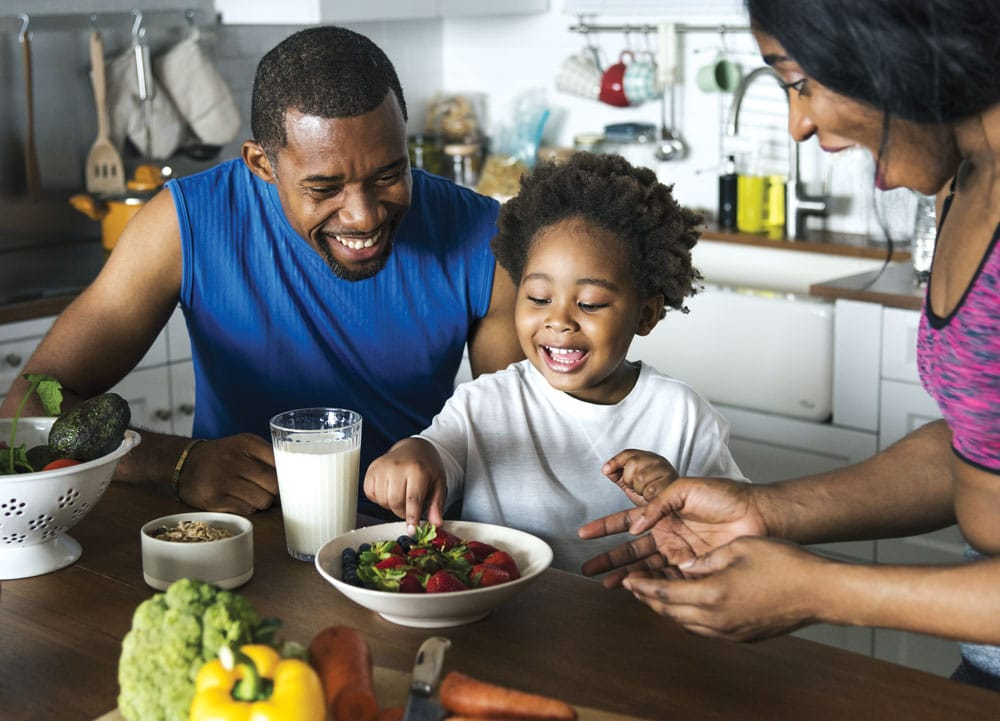 family eating bowl of strawberries in kitchen