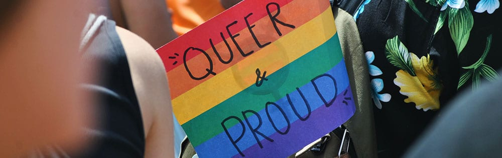 queer and proud sign parade