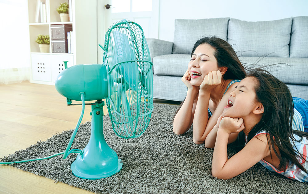 mom daughter hot in front of fan blowing