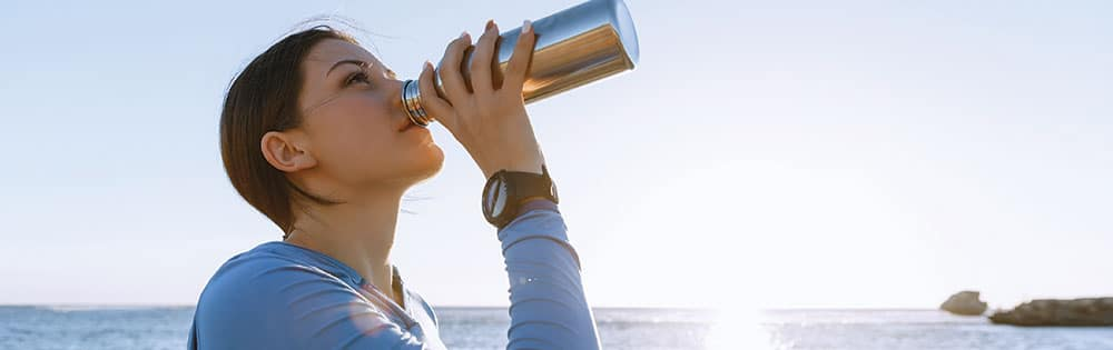 woman drinking from a water bottle near a lake