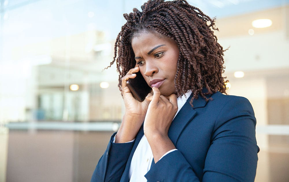 woman work clothes on phone worried