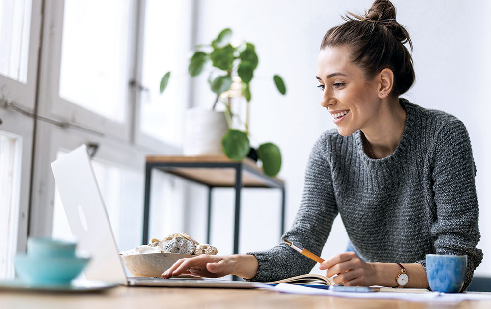 woman working on laptop from home smiling