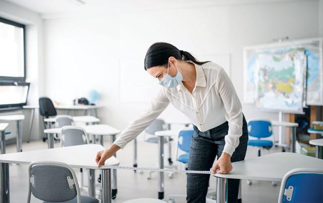 teacher wears mask measures distance between desks