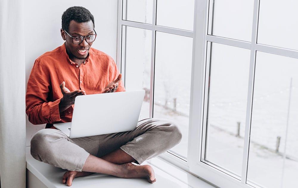 guy sitting with laptop wearing orange shirt