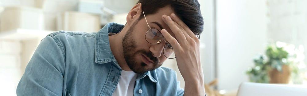man stressed wears glasses hand on head