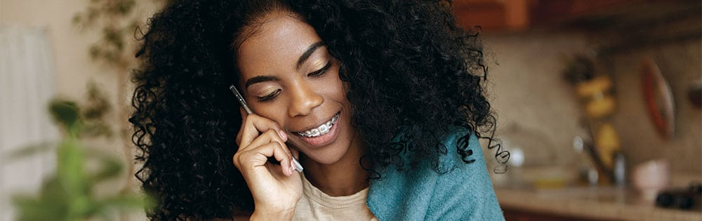 woman with braces talking on phone at home