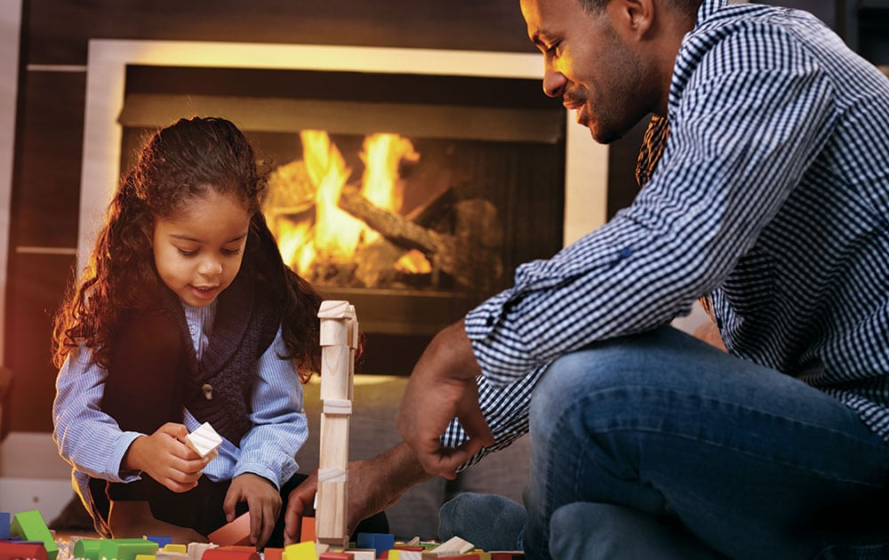 dad and daughter play blocks near fireplace