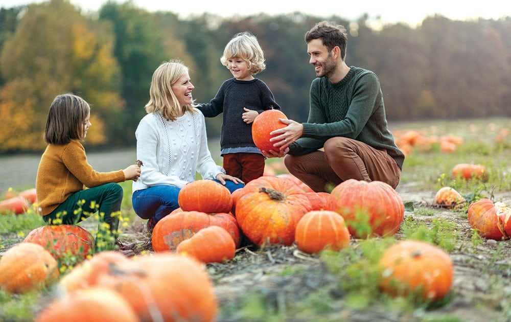young family at pumpkin patch